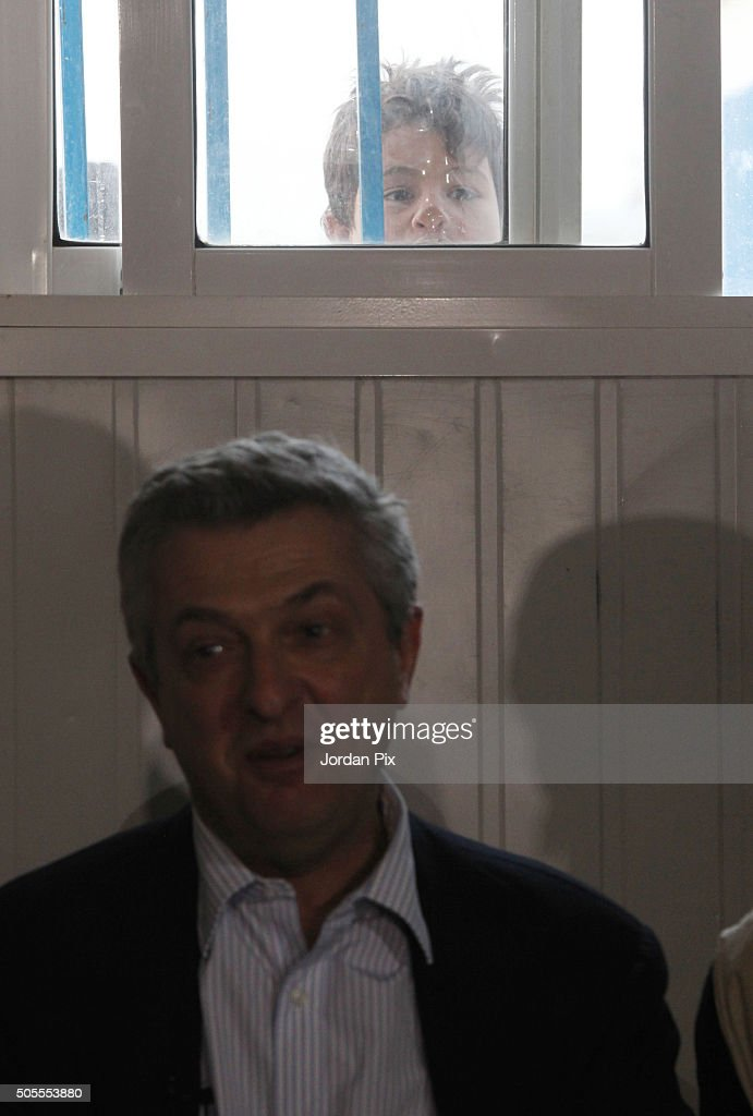 A young boy peers through a window as Filippo Granti the new UNHCR High Commissioner visits the Zaatari camp for Syrian refugees on January 18 2016...