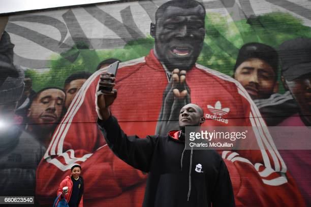 A young boy photo bombs grime artist Stormzy as he visits a mural depicting a scene from his video 'Shut Up' at Smithfield on March 30 2017 in Dublin...