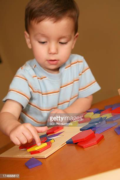 Young Boy Placing a Colored Block Down