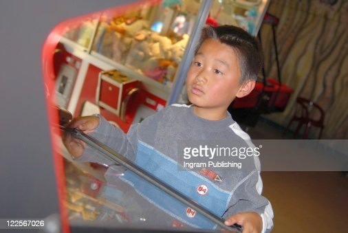 Young boy playing arcade game : Stock Photo
