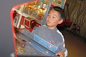 Young boy playing arcade game