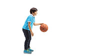 Full length profile shot of a young boy playing basketball isolated on white background