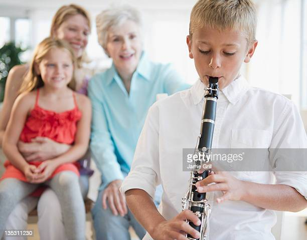 Young boy playing clarinet for family