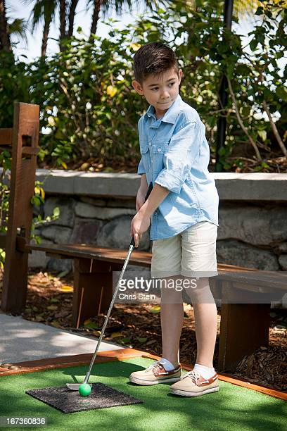 Young Boy playing miniature golf