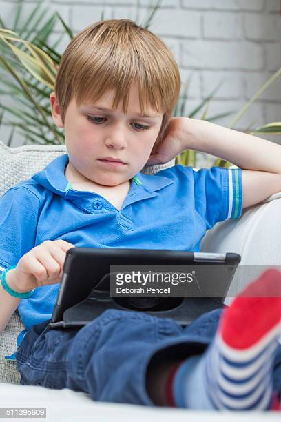 Young boy playing on digital tablet