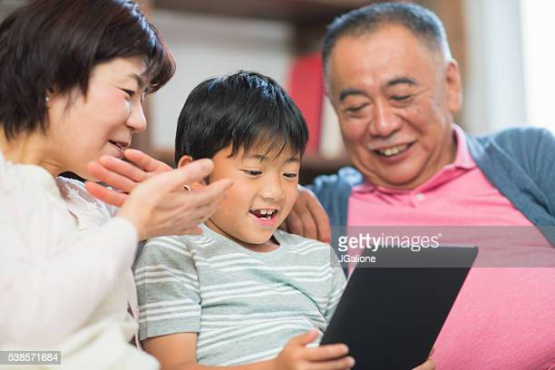 Young boy playing on digital tablet with Grandparents
