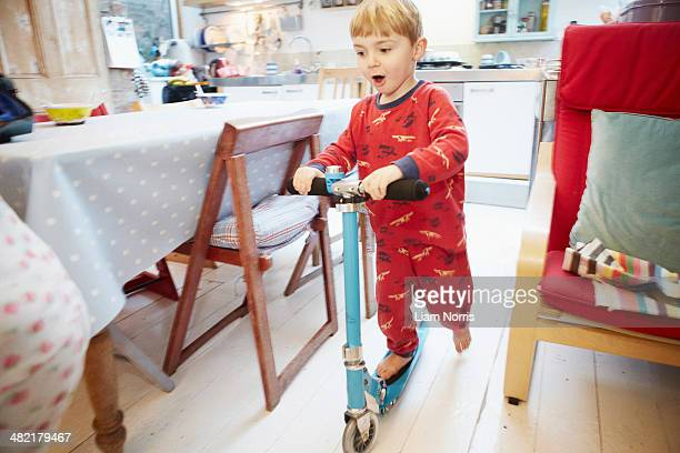 Young boy playing on scooter in kitchen