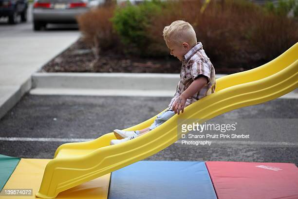 Young boy playing on yellow slide