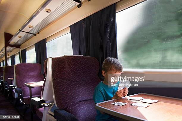 Young boy playing patience on train