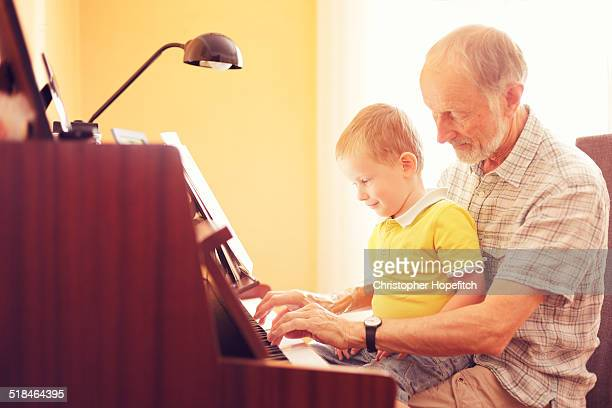Young boy playing the piano with his grandfather