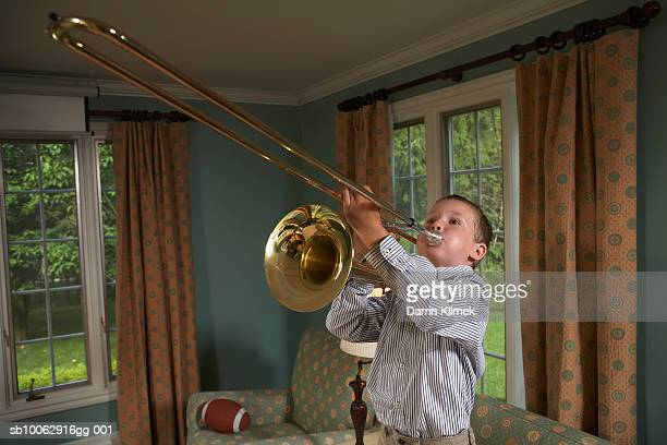 Young boy (6-7 years) playing trombone in living room