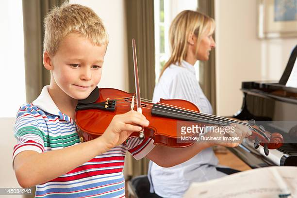 Young boy playing violin accompanied by teacher