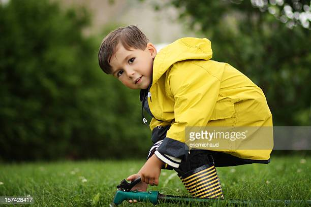 Young boy playing with a hose pipe