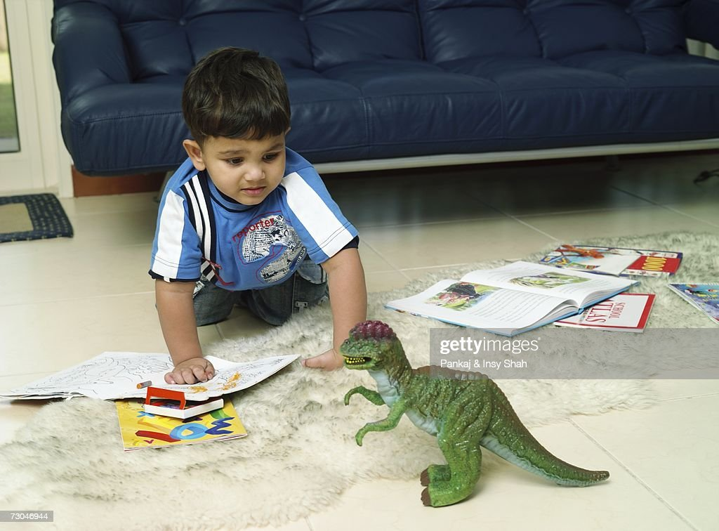 Young Boy playing with a toy dinosaur : Stock Photo