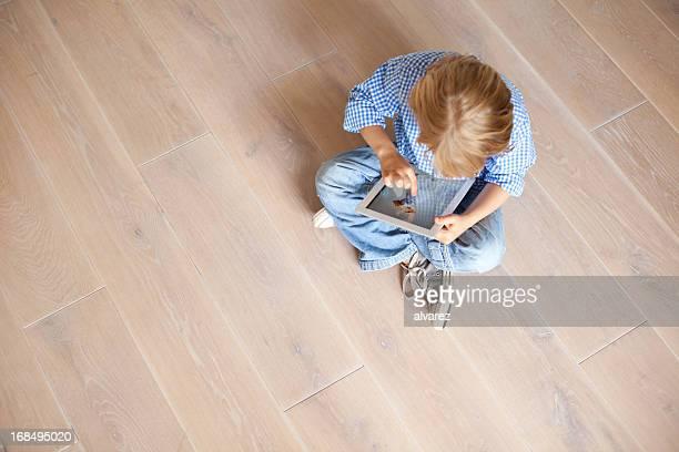 Kleiner Junge spielt mit digitalen tablet