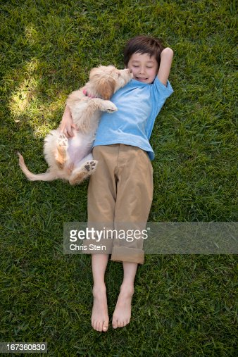 Young boy playing with his puppy : Stock Photo