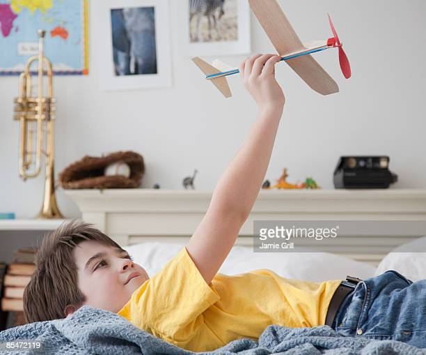 Young Boy Playing with Model Airplane in Bedroom