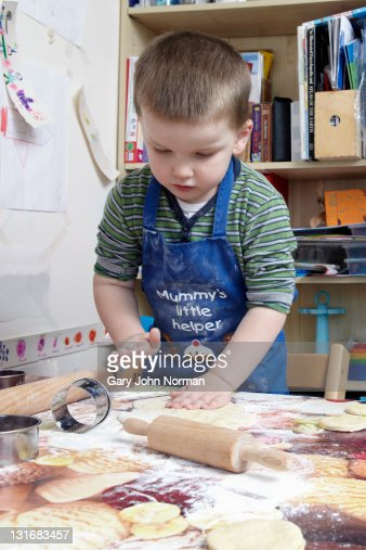 young boy playing with pastry dough. : Bildbanksbilder