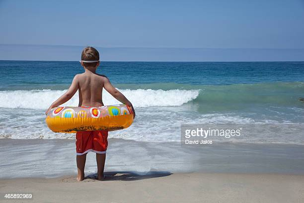 Young boy playing with rubber ring at beach