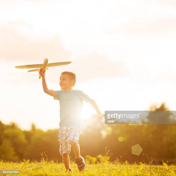 Young boy playing with toy airplane outside
