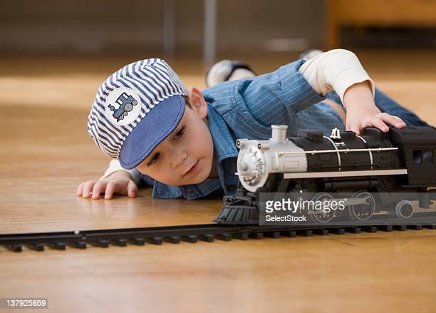 Kleiner Junge spielt mit Spielzeug-Züge