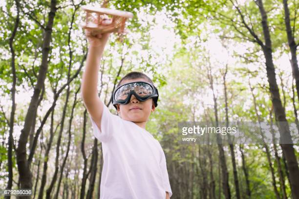 Young boy playing wooden airplane with pilot dressed