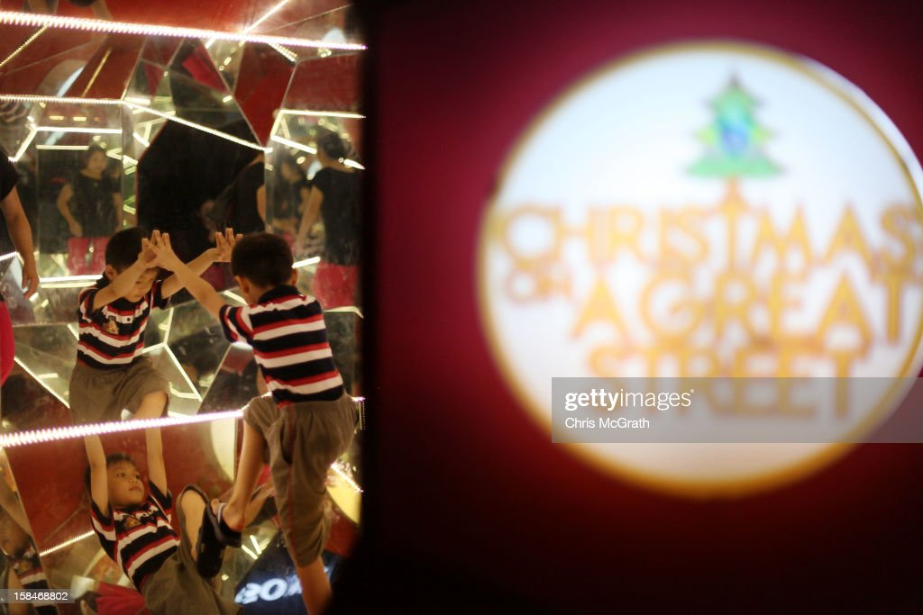 A young boy plays amongst a mirrored nativity scene setup along Orchard road on December 17, 2012 in Singapore.