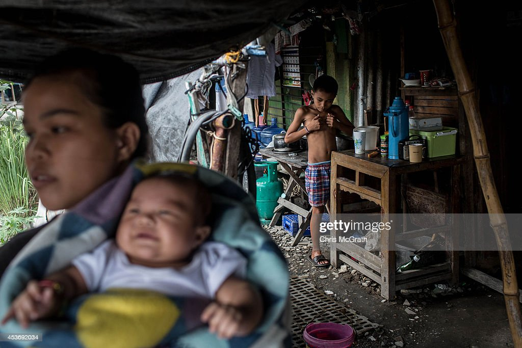 A young boy plays around at his temporary home in the San Jose evacuation complex on August 16, 2014 in Tacloban, Leyte, Philippines. Many families are still housed in temporary tent housing in the San Jose district. The families have been told that they will be rehoused before the visit of Pope Francis. Residents of Tacloban city and the surrounding areas continue to focus on rebuilding their lives nine months after Typhoon Haiyan struck the coast on November 8, 2013, leaving more than 6000 dead and many more homeless. With many businesses and government operations back up and running and with the recent start of the years typhoon season, permanent housing continues to be the main focus with many families still living in temporary accommodation. As well as continuing recovery efforts Leyte is preparing for the arrival of Pope Francis, who will visit the region from January 15- 19.