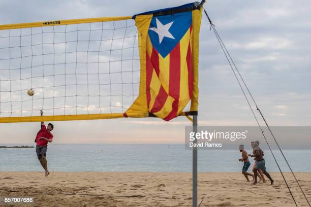 Young boy plays beach volley ball with a Catalan Proindependence flag known as 'Estelada' tied to the net as a regional general strike to protest...