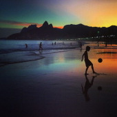 A young boy plays football at sunset on June 8 2014 in Rio de Janeiro Brazil