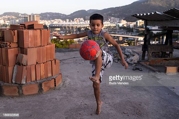 A young boy plays football in the Mangueira pacified community or shantytown which is located close to the famed Maracana Stadium on November 2 2013...