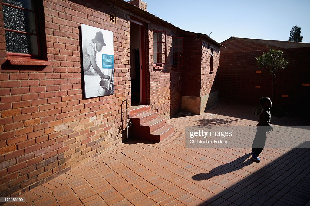A young boy plays in the back yard of the 'Mandela House' museum at 8115 in Vilakazi Street in the Orlando West section of Soweto Township on July 2, 2013 in Soweto, Johannesburg, South Africa. 8115 is the location of the first house owned by former South African President Nelson Mandela where he lived for 44 years from 1946 to 1990. The 'Mandela House', now a museum is managed by the Soweto Heritage Trust which has seen an increase in vistors both local and international since Mandela was hospitalized with a lung infection on June 8, 2013 and still remains in a critcal condition.