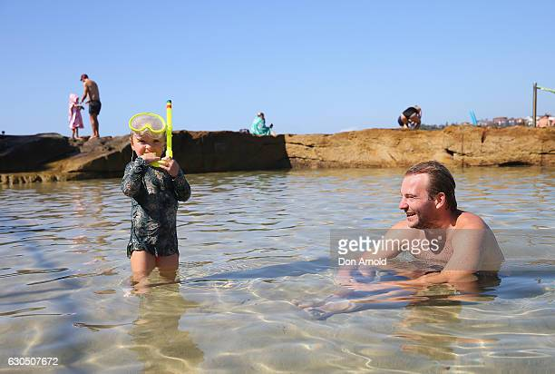 A young boy plays in the rock pools with his father at Bondi Beach on December 25 2016 in Sydney Australia Bondi Beach is a popular tourist...