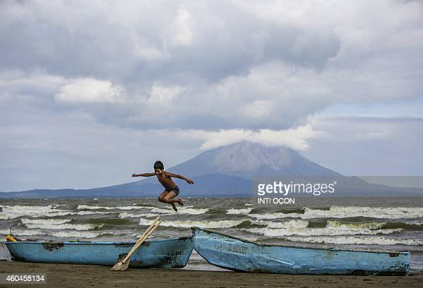 A young boy plays near two fishing boats along the shore of Cocibolca lake in Rivas Nicaragua on December 11 2014 The inhabitants of the area are...