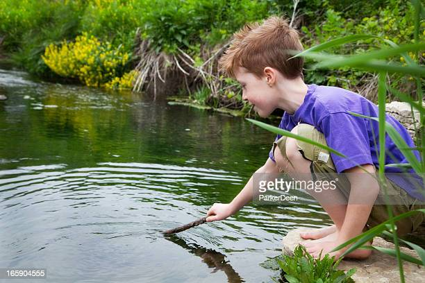 Young boy plays near water and greenery