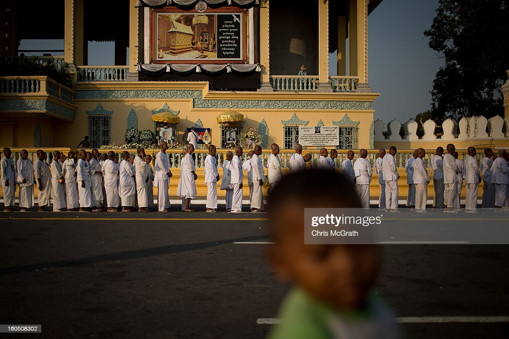 A young boy plays on the street in front of a line of nuns waiting outside the Royal Palace before be allowed to enter the cremation site to pay their final respects to former King Norodom Sihanouk on February 2, 2013 in Phnom Penh, Cambodia. The former kings coffin was transported to the cremation site yesterday after being paraded through the capital in a lavish funeral procession. The cremation will take place on Monday the 4th of February, the funeral pyre will be lit by his wife and son King Norodom Sihamoni.