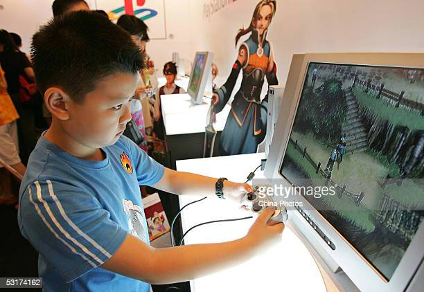 A young boy plays Sony's Playstation 2 video game system at the 2005 Shanghai Animation FairJune 30 2005 in Shanghai China China has a population of...