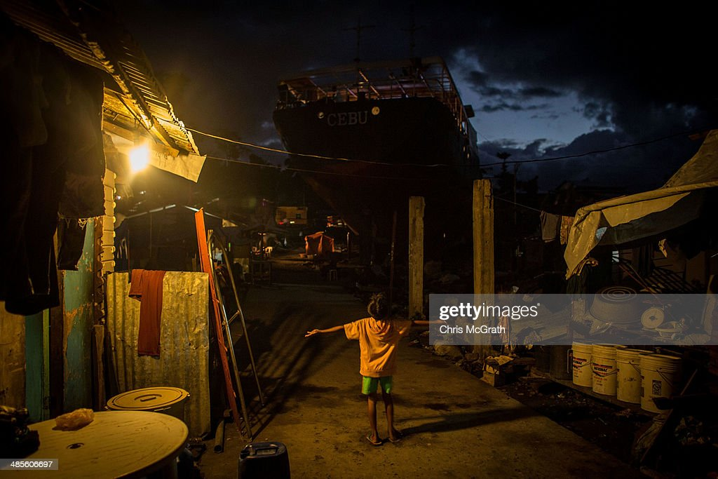 A young boy plays under a light in the coastal area renamed by residents ' Yolanda Village' on April 19, 2014 in Tacloban, Leyte, Philippines. People continue to rebuild their lives five months after Typhoon Haiyan struck the coast on November 8, 2013, leaving more than 6000 dead and many more homeless. Although many businesses and services are functioning, electricity and housing continue to be the main issues, with many residents still living in temporary housing conditions due to 'No Build' areas preventing them from rebuilding their homes. This week marks Holy Week across the Philippines and will see many people attending religious activities.