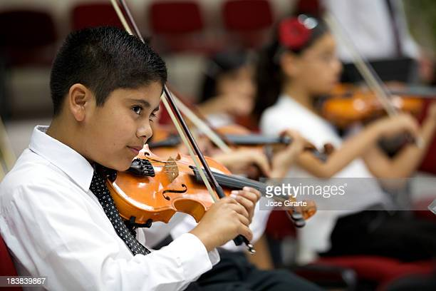 A young boy plays violin and stares outward