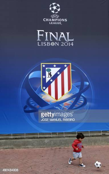 A young boy plays with a ball in front of a banner with the logo of the Atletico Madrid football club announcing the upcoming UEFA Champions League...