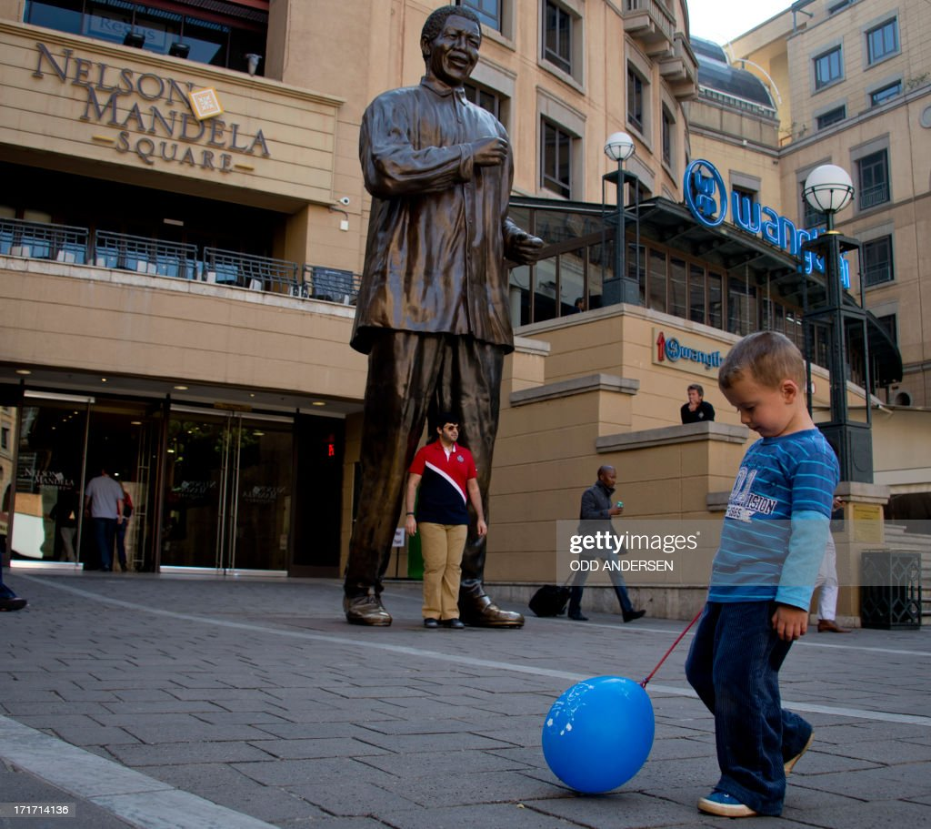 A young boy plays with a balloon in front of a giant bronze statue of Nelson Mandela at Nelson Mandela square in the north Johannesburg suburb of Sandton on June 28, 2013. Mandela is receiving treatment at the Mediclinic heart hospital in Pretoria. Mandela's close family gathered yesterday at his rural homestead to discuss the failing health of the South African anti-apartheid icon who was fighting for his life in hospital. Messages of support poured in from around the world for the Nobel Peace Prize winner, who spent 27 years behind bars for his struggle under white minority rule and went on to become South Africa's first black president.