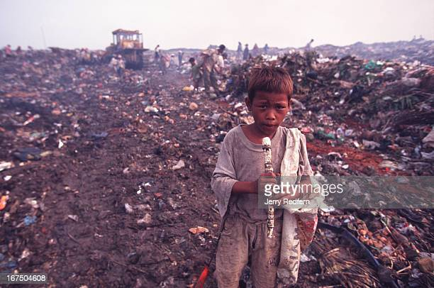 A young boy plays with a broken recorder he found while scavenging in the Stung Meanchey dumpAbout 200 families make their living at the dump taking...