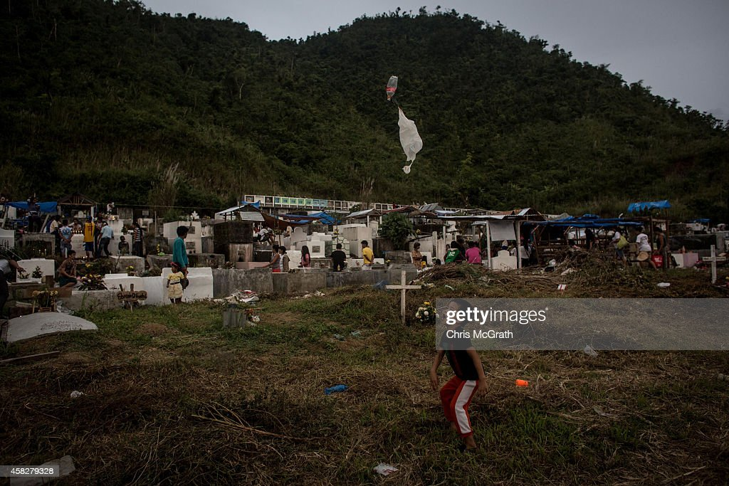 TACLOBAN LEYTE PHILIPPINES NOVEMBER 02 A young boy plays with a toy in front of a single white cross erected to honour Typhoon Yolanda victims on the...