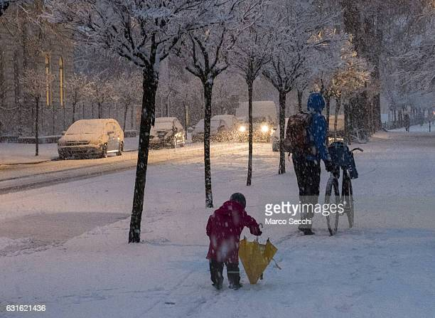 A young boy plays with his umbrella under heavy snow on January 13 2017 in Ljubljana Slovenia Most of Slovenia was covered by heavy snowfalls for the...