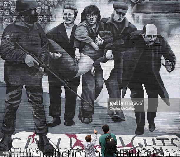 A young boy points at a mural depicting a scene from Bloody Sunday as final preparations for the funeral of the late retired Bishop of Derry Dr...