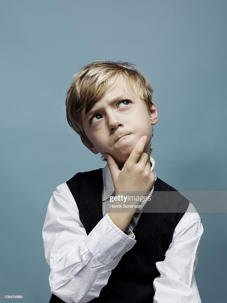 Young boy pondering with hand on chin