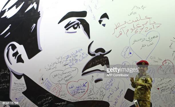 A young boy poses for a photo after writing a comment on a wall bearing a portrait of Qatar's Emir Sheikh Tamim bin Hamad Al Thani which has become...
