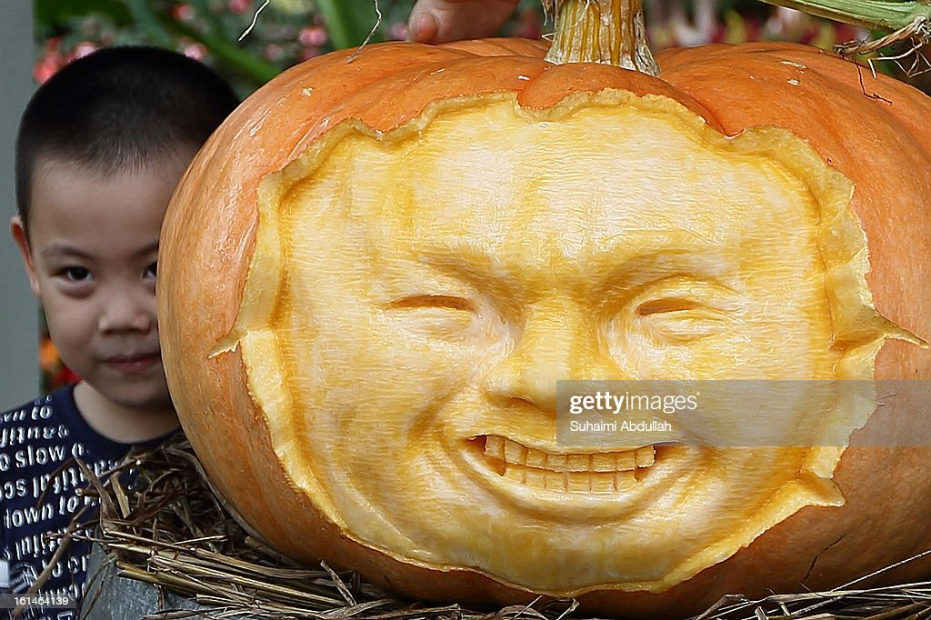 A young boy poses for a photograph with a face carved pumpkin at the Sentosa Flowers exhibition at Palawan Beach on February 11, 2013 in Singapore. Millions of spring flowers decorate the island in celebration of the Chinese New Year, the year of the Snake.