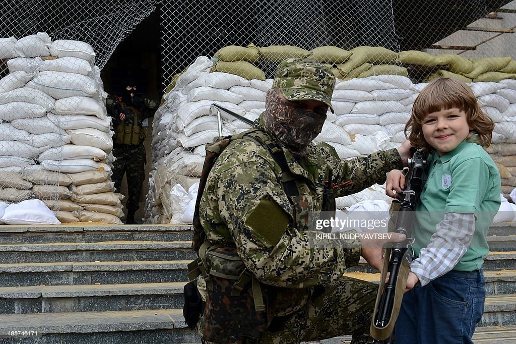 A young boy poses with an armed man in military fatigue guarding a barricade outside the regional administration building in the eastern Ukrainian city of Slavyansk on April 20, 2014. Pro-Moscow rebels in Slavyansk declared a curfew there Sunday, after a gun battle with unidentified attackers killed two militants. Separatist rebels leader Vyacheslav Ponomaryov told reporters that 'the curfew comes into effect today'. AFP PHOTO / KIRILL KUDRYAVTSEV