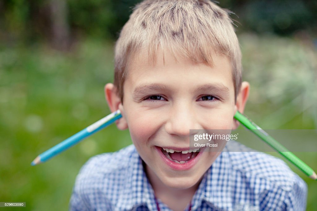 Young boy (8-9) posing with two pens stuck in his ears : Bildbanksbilder